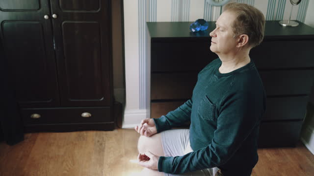 man sat on chair meditating in bedroom - mindfulness stock videos & royalty-free footage