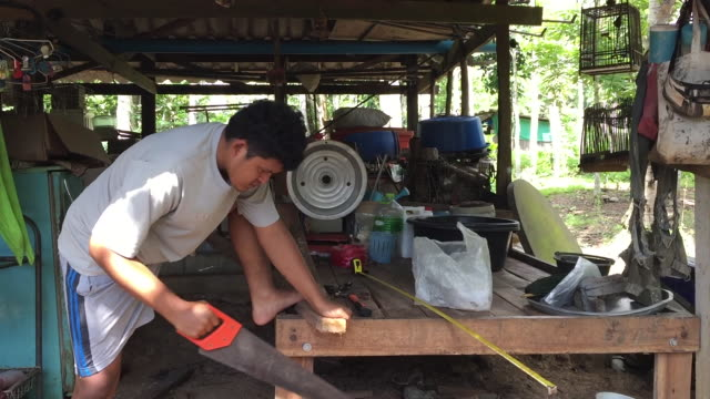 man sawing a wooden block with a hand saw - handle stock videos & royalty-free footage