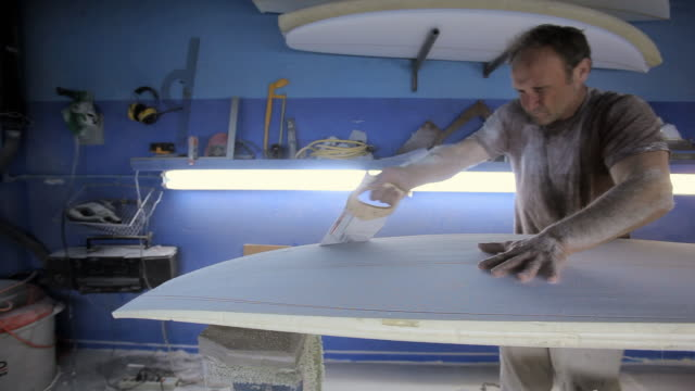 Man sawing new surfboard