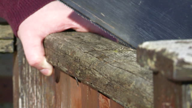 man saws into an old wooden beam - fence stock videos & royalty-free footage