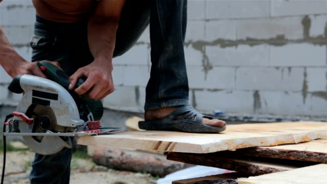 man saws plank with a circular saw. - timber stock videos and b-roll footage