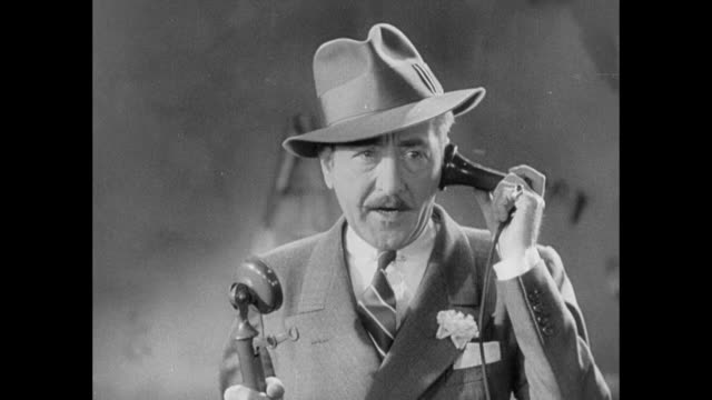 "vídeos de stock e filmes b-roll de 1931 man (adolph menjou) says into phone: ""tell her nothing. she's a woman you fool."" - 1931"