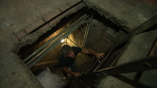 vidéos et rushes de a man scales two ladders in an underground tunnel. - échelle