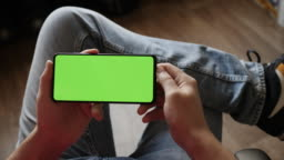 Man Scanning Fingerprint on smartphone with Green Mock-up Screen, Doing Swiping, Scrolling Gestures. Guy Mobile Phone, Internet Social. Scan Fingerprint Biometric Identity Approval. Security Concept