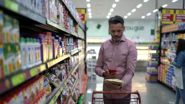 man scanning product using smartphone in the supermarket - composition stock videos & royalty-free footage