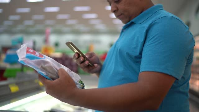 vidéos et rushes de produit de balayage d'homme utilisant le smartphone dans le supermarché - codage et codification