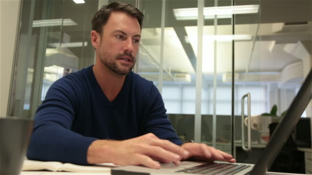 man scans laptop, points at screen - concentration stock videos & royalty-free footage
