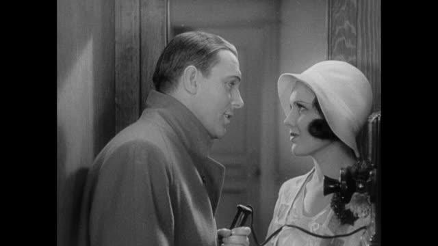 1931 man (pat o'brien) schmoozes fiance (mary brian) in telephone box - 1931 stock videos & royalty-free footage