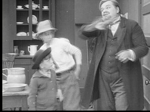1913 b/w montage ms man (fatty arbuckle) scolding and threatening boys. hits head into door / usa - fatty arbuckle stock videos and b-roll footage