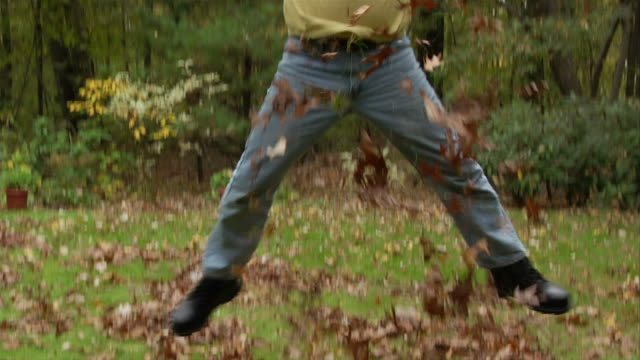 Man scooping up raked leaves and jumping as he tosses them in air / smiling as leaves rain down over him
