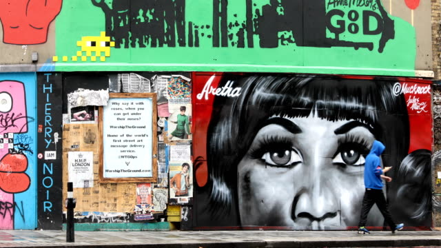 a man scooters past a piece of street art by artist jules muck in collaboration with global street art paying tribute to the late aretha franklin in... - respekt stock-videos und b-roll-filmmaterial