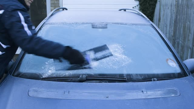 man scraping ice from car windscreen. - frost stock videos & royalty-free footage