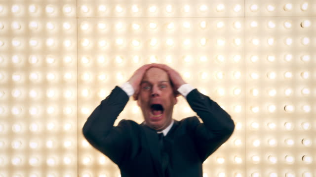 stockvideo's en b-roll-footage met man screaming in front of lightwall - schreeuwen