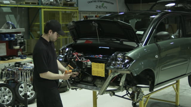 ms man screwing battery into front of electric car on production line, st. jerome, quebec, canada - 自動車工場点の映像素材/bロール