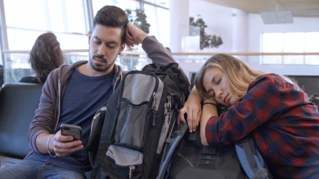 mannen rullning telefonen vid flygplats grinden väntar på boarding medan kvinnan sover på hennes ryggsäck - vänta bildbanksvideor och videomaterial från bakom kulisserna