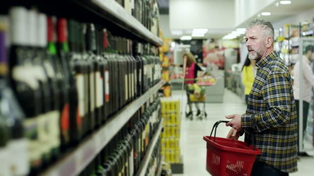 vidéos et rushes de homme à la recherche d'un bon vin en supermarché - panier courses