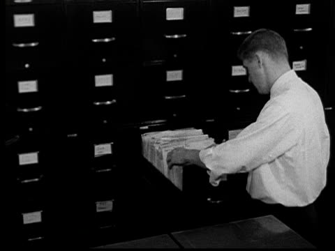 1955 MS Man searching for file/ Man grabbing file, closing drawer, and walking away/ Buffalo, New York