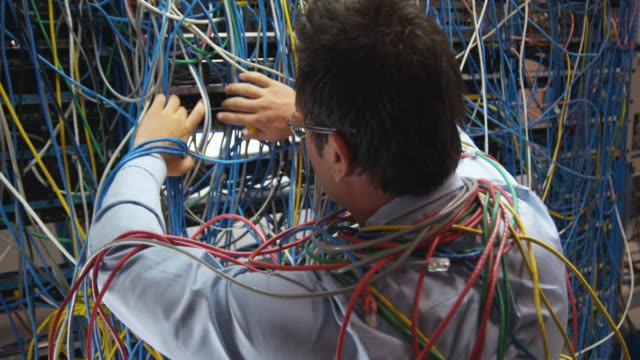ms man searching through server wall covered in cables, sydney, australia - chaos stock-videos und b-roll-filmmaterial