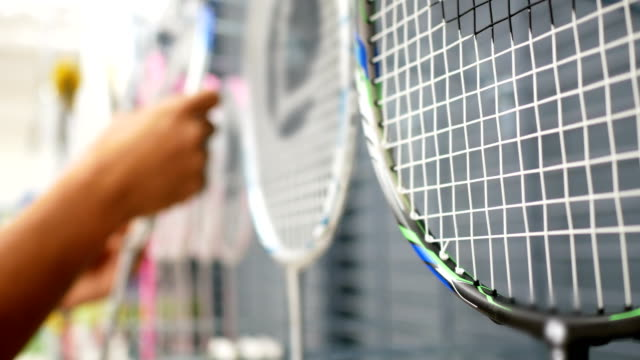 vídeos de stock e filmes b-roll de man select a new racket for badminton in the sportswear store - raqueta