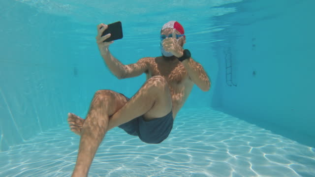 man selfie underwater with anti covid face mask protection in a summer swimming pool - hygiene stock videos & royalty-free footage