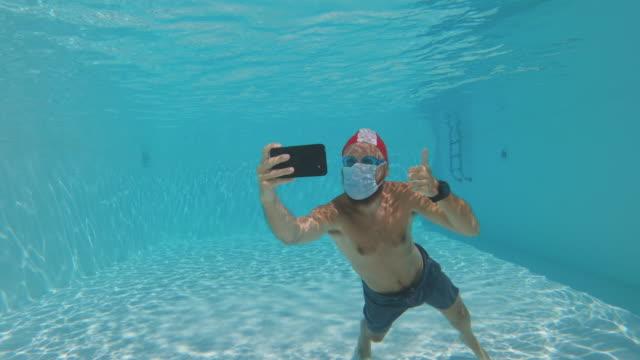 vídeos de stock, filmes e b-roll de homem selfie debaixo d'água com proteção anti covid máscara facial em uma piscina de verão - anti higiênico