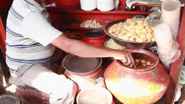 man selling kanji vada in the market, delhi, india - marktstand stock-videos und b-roll-filmmaterial