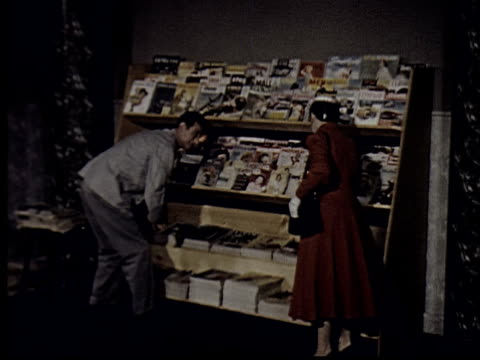 ms, man selling magazine to woman at news stand - zeitschrift stock-videos und b-roll-filmmaterial