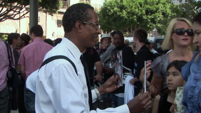 man selling memorial booklets to crowds outside the staples center before michael jackson memorial service/ ms zi zo stall selling tshirts and... - arms crossed stock videos & royalty-free footage