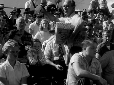 b/w ms 1956 man selling popcorn to audience in bleachers - selling stock videos & royalty-free footage