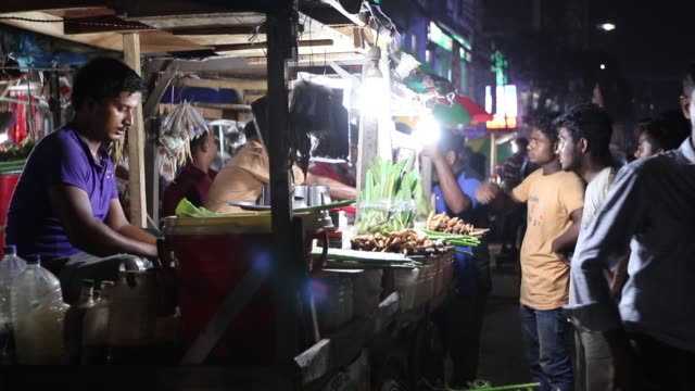 man selling sherbet and herbal ingredients of medicinal qualities on the footpath of karwan bazar, dhaka. - nachtmarkt stock-videos und b-roll-filmmaterial