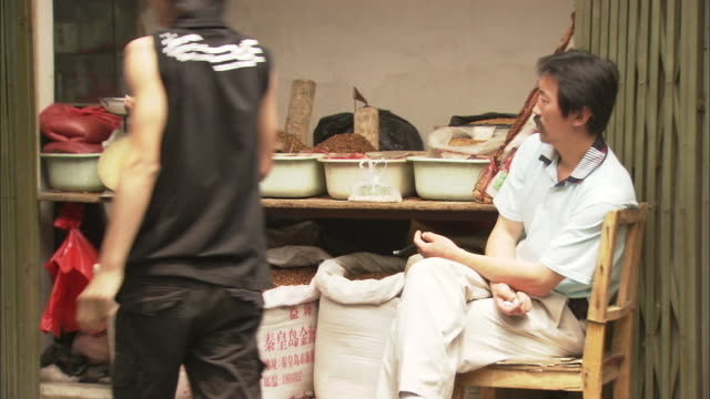 ms man selling tobacco in market, beijing, china - tre quarti video stock e b–roll