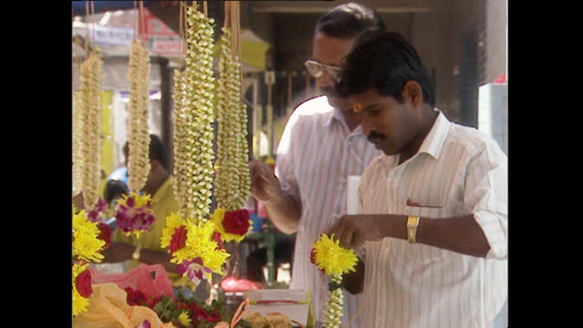 man sells flower garlands from market stall in kuala lumpur; 1996 - 1996 stock videos & royalty-free footage