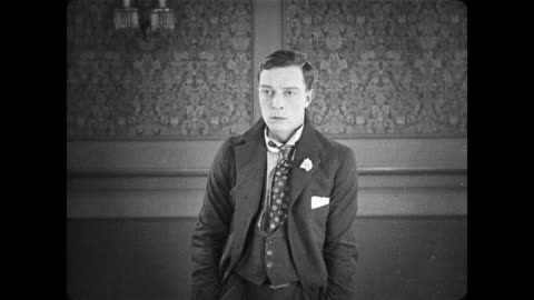 1922 man (buster keaton), sensing an ominous cold shoulder from the people in the room, decides on a hasty exit - slapstick comedy stock videos & royalty-free footage