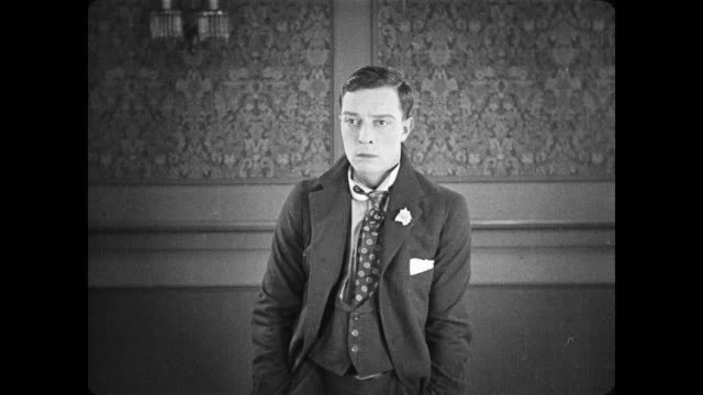 1922 man (buster keaton), sensing an ominous cold shoulder from the people in the room, decides on a hasty exit - slapstick stock videos & royalty-free footage