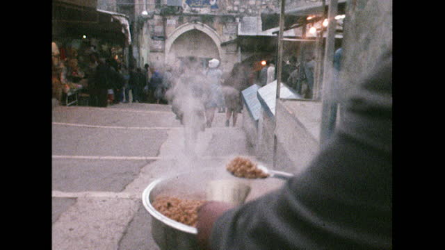 man serves hot food in a market square, israel; 1969. - market stock videos & royalty-free footage