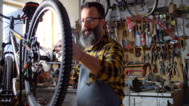 slo mo man servicing a bike in the workshop - 45 49 years stock videos & royalty-free footage