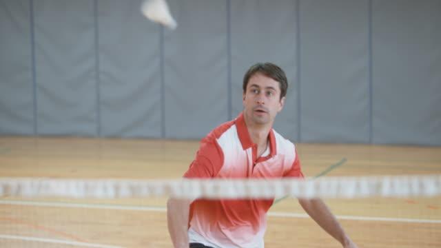 vídeos de stock, filmes e b-roll de o homem servindo e jogando badminton indoor - badmínton esporte