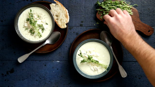 man serving creamy caulflower and broccoli with feta soup - cucina mediterranea video stock e b–roll