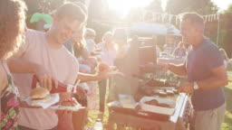 Man serving food from barbecue stall at summer garden fete - shot in slow motion