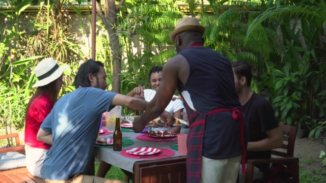 man serving food to his friends at outdoor - apron stock videos & royalty-free footage