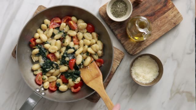 man serving gnocchi with creamy tomato and spinach sauce - cucina mediterranea video stock e b–roll