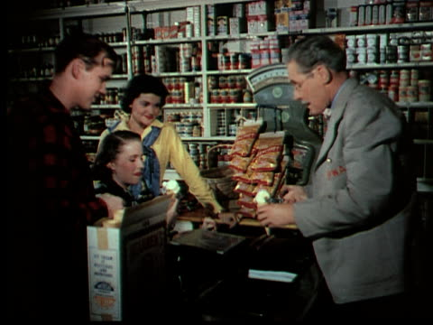 1949 montage ms man (parker fennelly) serving ice cream to three teenagers in country store - generi alimentari video stock e b–roll