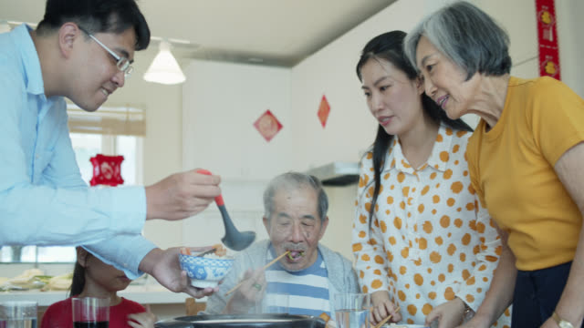 man serving parents and children at chinese new year meal at home - taiwan stock videos & royalty-free footage