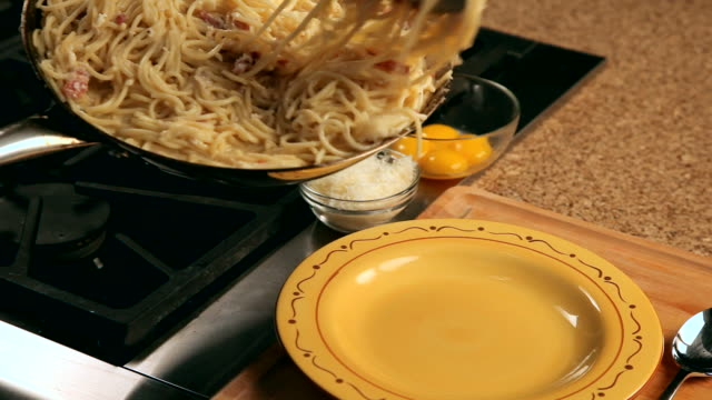 pov man serving pasta carbonara with tongs - serving tongs stock videos & royalty-free footage