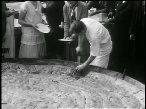 b/w 1929 man serving slices of world's largest pie outdoors / albion, ny / newsreel - world record stock videos and b-roll footage