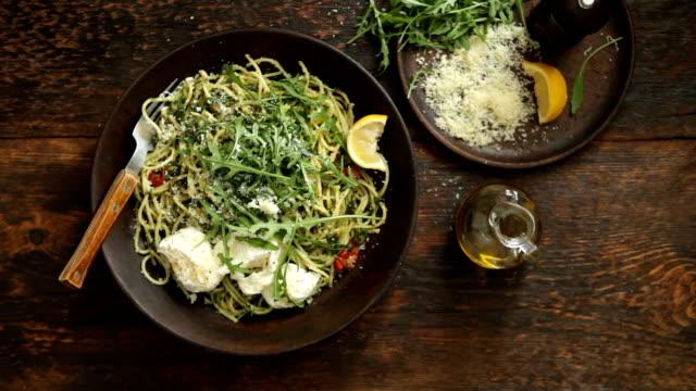 Man serving spaghetti with pesto, roasted tomatoes, fresh arugula and mozzarella