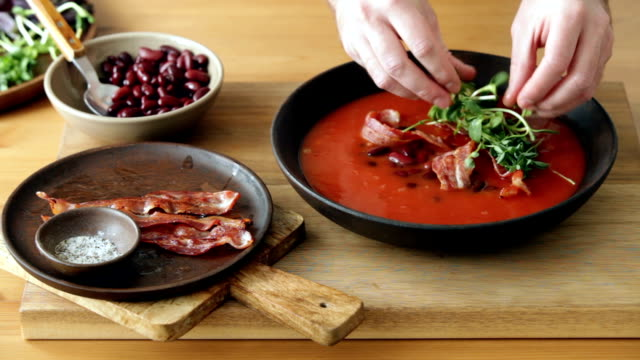man serving spicy tomato, bean, herb and fried bacon soup - tomato soup stock videos and b-roll footage