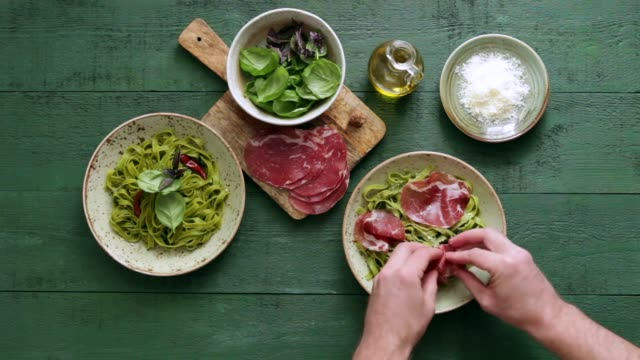 man serving spinach pasta with basil pesto and prosciutto - cucina mediterranea video stock e b–roll