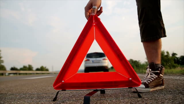 man set warning triangle on the road - safety stock videos & royalty-free footage