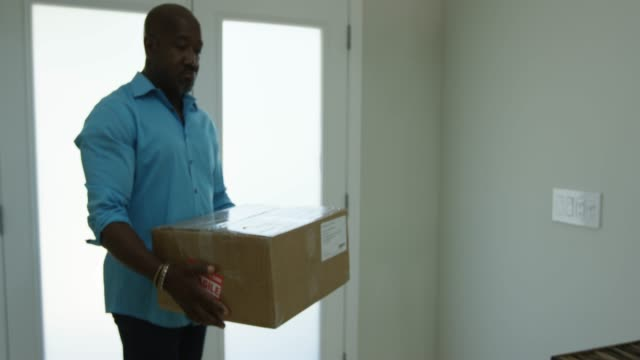 Man sets down package near front door